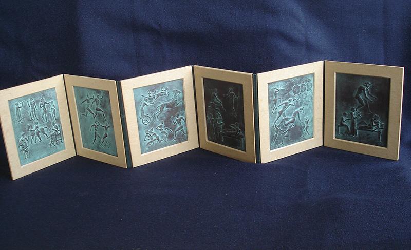(2) (1)の内部に収納されている古代オリンピックの様子を刻んだ6枚の青銅板のレリーフ