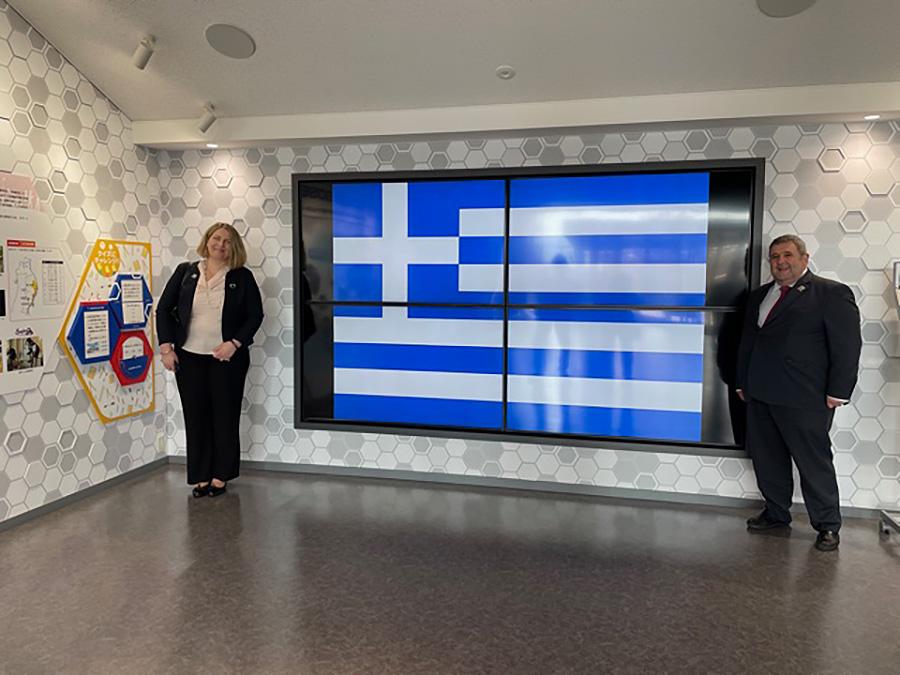 モニターに映し出されたギリシャ国旗の傍らに立つカキュシス大使・ヤナカル夫人 © 稲沢市