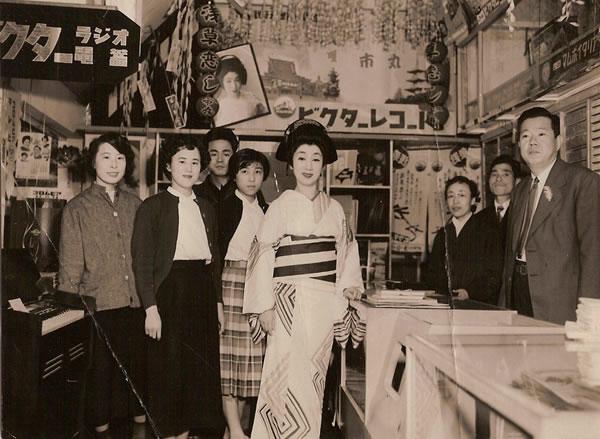 Στο θρυλικό δισκοπωλείο YORO-Do στην Ασακούσα: Επίσκεψη της γνωστής τραγουδίστριας ICHIMARO τη δεκαετία του 1930. Tο κατάστημα άνοιξε το 1912 και σήμερα υποστηρίζει τους νέους τραγουδιστές και τραγουσίστριες ΕΝΚΑ.